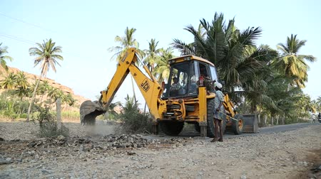 экскаватор : HAMPI, INDIA - 28 JANUARY 2015: Digger digging on the road in Hampi.