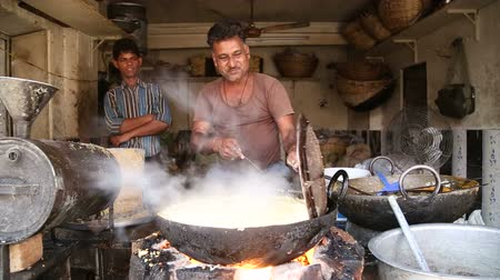 cooking pots : JODHPUR, INDIA - 5 FEBRUARY 2015: Indian man frying food in a large pot.