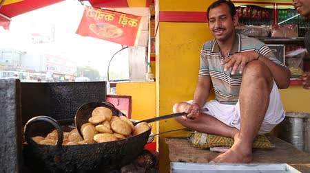 stánek s jídlem : JODHPUR, INDIA - 11 FEBRUARY 2015: Smiling Indian man frying local food at street stand in Jodhpur.