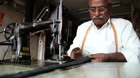 local : JODHPUR, INDIA - 11 FEBRUARY 2015: Indian man sewing on a sewing machine, closeup.