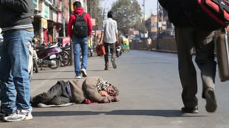 evsiz : JODHPUR, INDIA - 11 FEBRUARY 2015: Man sleeping at street in Jodhpur while people pass by. Stok Video