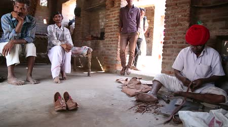 manmade : JODHPUR, INDIA - 13 FEBRUARY 2015: Group of Indian men sitting in house and standing at doorstep.