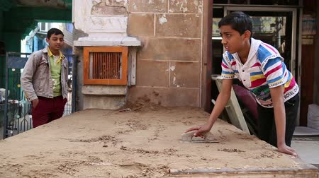 emek : JODHPUR, INDIA - 17 FEBRUARY 2015: Indian boy realigning sand with a trowel at street in Jodhpur.