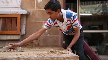 indian ethnicity : JODHPUR, INDIA - 17 FEBRUARY 2015: Indian boy realigning sand with a trowel at street in Jodhpur.