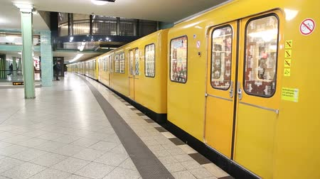 метро : BERLIN, GERMANY - 28 JANUARY 2015: Elderly man entering yellow U-bahn train in station and train exiting station.