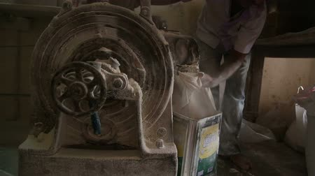 bombay : MUMBAI, INDIA - 7 JANUARY 2015: Man working on a machine that processes grains to flour in Mumbai, India.
