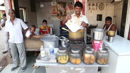 comerciante : MUMBAI, INDIA - 7 JANUARY 2015: Man making chai in tea shop on the streets of the capital.