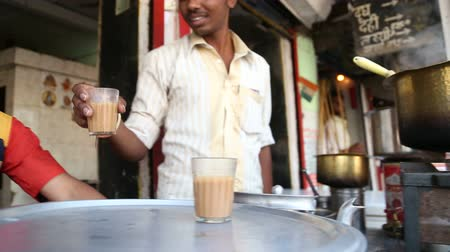 comerciante : MUMBAI, INDIA - 7 JANUARY 2015: Man selling tea in a tea shop on the streets of the capital.