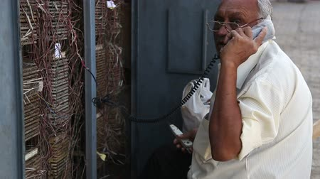 earpiece : MUMBAI, INDIA - 7 JANUARY 2015: Man talking on an old-fashioned phone on the street of Mumbai.