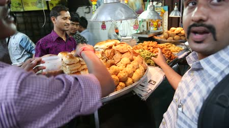 comerciante : MUMBAI, INDIA - 8 JANUARY 2015: Indian men buying food and eating in front of a street food stand.