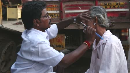 kolkata : MUMBAI, INDIA - 8 JANUARY 2015: Indian men shaving beard at the street of Mumbai.