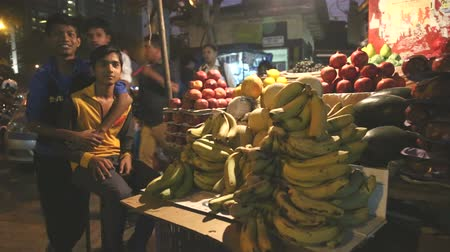 comerciante : MUMBAI, INDIA - 8 JANUARY 2015: Indian teenage boys at a fruit stand of a busy street market.