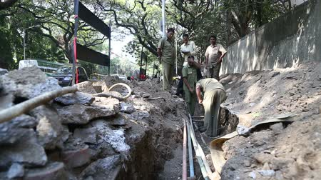 навес : MUMBAI, INDIA - 9 JANUARY 2015: Workers digging road in reconstruction while cars pass by.