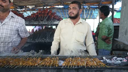 comerciante : MUMBAI, INDIA - 9 JANUARY 2015: Man grilling and pointing skewers with meat towards the camera. Vídeos
