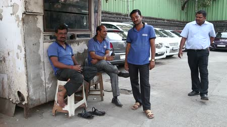 skútr : MUMBAI, INDIA - 9 JANUARY 2015: Four Indian men posing at auto mechanics garage.