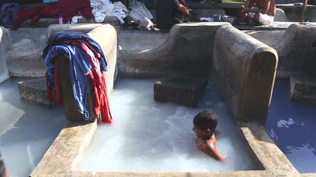 bombay : MUMBAI, INDIA - 10 JANUARY 2015: Boy playing in a washing pool filled with detergent in slum of Mumbai.