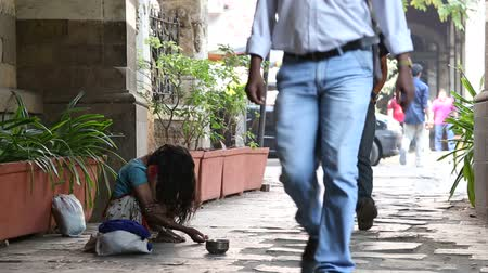 segít : MUMBAI, INDIA - 10 JANUARY 2015: Young girl begging on the street of Mumbai while people pass by. Stock mozgókép