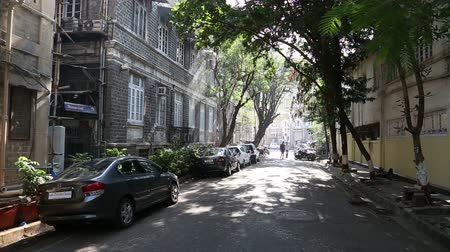 vista frontal : Peaceful suburban street in Mumbai, with cars and apartment buildings.