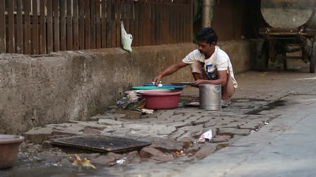 чистый : MUMBAI, INDIA - 10 JANUARY 2015: Indian man washing dishes by a street drain-away in Mumbai. Стоковые видеозаписи