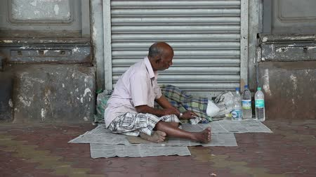 hobo : MUMBAI, INDIA - 10 JANUARY 2015: Man sitting on newspaper on the street and eating.