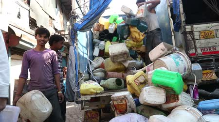 bombay : MUMBAI, INDIA - 12 JANUARY 2015: Group of men unloading products from a truck at street in Mumbai.