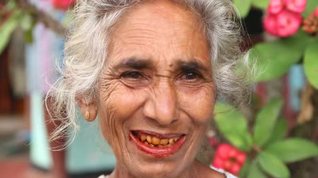 betel : ELLA, SRI LANKA - MARCH 2014: Portrait of an elderly woman with teeth eaten by paan. Betel nut and other spices eat away teeth and die them red.