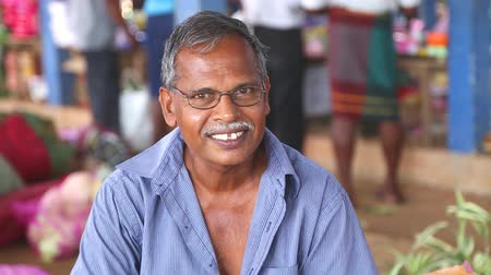 asian and indian ethnicities : HIKKADUWA, SRI LANKA - MARCH 2014: Portrait of local elderly smiling man at Hikkaduwa Sunday market, known for its wide range of fresh and varied produce.