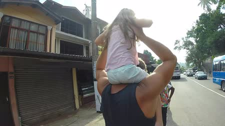 omuzlar : KANDY, SRI LANKA - FEBRUARY 2014: Man carrying little blond girl on his shoulders while walks down the street.