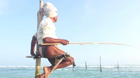 Ланка : GALLE, SRI LANKA - MARCH 2014: Elderly fisherman on a fishing pole in the ocean. Stilt fishing is a tradition that only about 500 fishing families in the district of Galle practice.