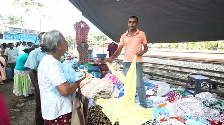 vasárnap : HIKKADUWA, SRI LANKA - FEBRUARY 2014: Local salesman showing and arranging textile at Hikkaduwa market. Hikkaduwa Sunday market is known for its wide range of supplies.