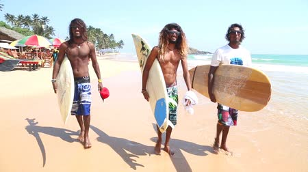 Ланка : MIRISSA, SRI LANKA - MARCH 2014: Three local surfers with boards and glasses and long hair, walking on the beach in Mirissa. Стоковые видеозаписи