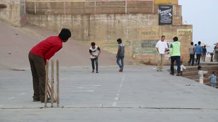 kriket : VARANASI, INDIA - 20 FEBRUARY 2015: Boys playing cricket on playground in Varanasi, with people passing by. Stok Video