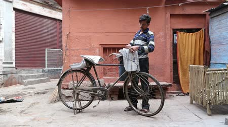 boletim informativo : VARANASI, INDIA - 20 FEBRUARY 2015: Delivery boy with bicycle sorting newspapers at street in Varanasi.