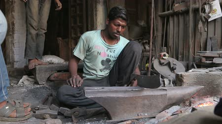 slicer : VARANASI, INDIA - 20 FEBRUARY 2015: Man shaping a blade with mallet on stone in workshop in Varanasi.
