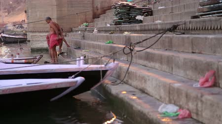 varanasi : VARANASI, INDIA - 22 FEBRUARY 2015: Men bathing on the ghats of Ganges river in Varanasi, surrounded with boats.