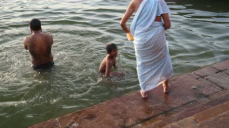wanna : VARANASI, INDIA - 22 FEBRUARY 2015: Man and boy bathing in Ganges, with woman approaching water. Wideo