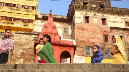 picturesque quarters : VARANASI, INDIA - 22 FEBRUARY 2015: Low angle view of people passing by street buildings in Varanasi. Stock Footage