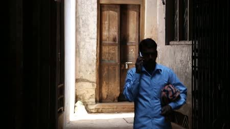 earpiece : VARANASI, INDIA - 22 FEBRUARY 2015: Man walking down the narrow street and talking on the phone.