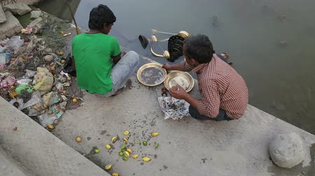 emek : VARANASI, INDIA - 19 FEBRUARY 2015: Indian boy and man cleaning decorative dishes at shore of Ganges in Varanasi. Stok Video