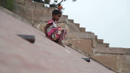 deslizamento : VARANASI, INDIA - 19 FEBRUARY 2015: Indian girl sliding down the slope on ghats of Ganges river in Varanasi.