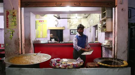 asian and indian ethnicities : VARANASI, INDIA - 19 FEBRUARY 2015: Indian man preparing local food at street stand in Varanasi.