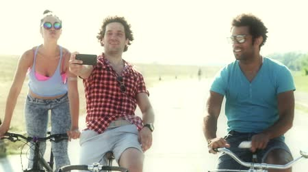telefone celular : Close up of three young adults cycling outdoors and having fun taking selfies, graded