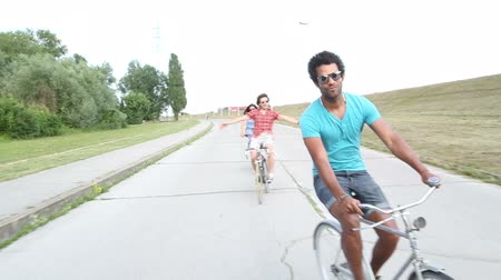 bisiklete binme : A wide shot of a group of young adults while they are cycling outdoors and having a great time. Stok Video