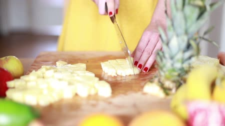 cutting up : Close-up of woman hands cutting pineapple on small pieces for fruit shake Stock Footage