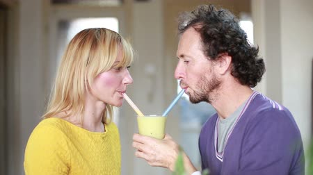 içme : Close-up of cute couple drinking smoothie from same drinking glass Stok Video