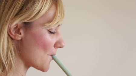 ağız : Close-up of profile face of a young woman drinking smoothie with a straw Stok Video