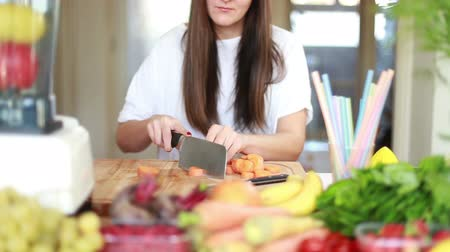 разделочная доска : Brunette woman cutting carrot into pieces on wooden board for fruit shake