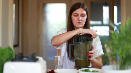 зеленый фон : Young brunette woman pouring green smoothie into glass Стоковые видеозаписи