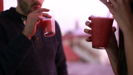белок : Close-up of young man and woman toasting and drinking fruit smoothie