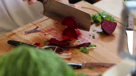 peeler : Close-up of woman hands cutting beetroot on wooden board
